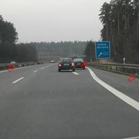 Messung März 2004, hinter Gebüsch silberner Wagen. Blitz-/Foto-Einheiten an Leitplanken.