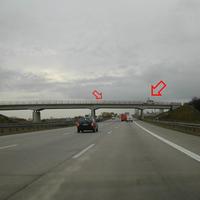 Anfahrtsansicht: verdächtiges Fahrzeug auf Brücke, eine Kamera am Brückengeländer erkennbar.