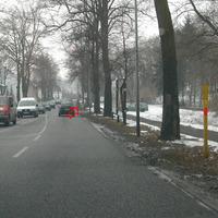 Anfahrtsansicht nach Ortseingang: verdächtig parallel parkender Pkw-Kombi zwischen den Bäumen.