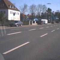 Messwagen ist der rote VW Golf am rechten Straßenrand hinter einem Anhänger geparkt. (Foto aus Gegenrichtung).