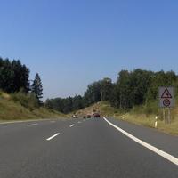 Anfahrtsansicht: plötzliches, gemeinschaftliches Bremsen aller Verkehrsteilnehmer; auf der Standspur fällt eine Pylone auf.