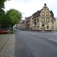 Anfahrtsansicht. Das Messfahrzeug steht direkt vor dem kleinen, roten Auto am rechten Fahrbahnrand.