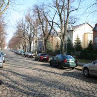 Anfahrtsansicht. Die Straße gehört zu einer Tempo 30 Zone. Auch geht es im Prinzip wegen des schlechten Straßenzustandes nicht viel schneller ohne den Wagen zu beschädigen.
