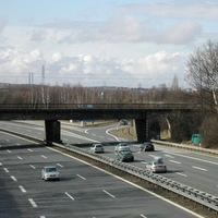 Gesamtansicht, Foto-/Blitz-Einheiten vor Brückenpfeiler im Schatten, grüner Bus rechts auf Feldweg