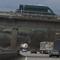 Vergrößerung: der Meßbeamte richtet gerade den Blitz-/Fotokasten am Ende vom Brückenpfeiler ein. Verdunkelte Scheiben am dunkelgrünen Großmeßbus....