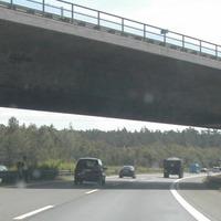 im Schatten der Brücke an Mittelleitplanke die Blitz-Foto-Einheit und Messpersonal, rechts Blitz-Foto-Einheit an Leitplanke,  Messwagen gut sichtbar.