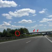 """Anfahrtsansicht: das geübte Adlerauge kann zwei """"typische"""" schwarze Punkte im Brückengeländer erkennen. Nur minimal schimmert der Meßbus durch die Bäume.  Der informierte Verkehrsteilnehmer wußte schon durch Antenne-Bayern Bescheid."""