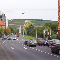 Fernansicht auf eine sehr stark befahrene Kreuzung in Würzburg. Der rote Pfeil zeigt auf den Ampelblitzer.
