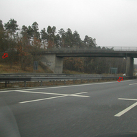 kleine Videokamera unten am Brückenfeiler, Kabel nach oben; grauer Messbus links hinten Bäumen