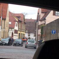 Eine Seltenheit: Die Polizei lasert in diesem Ort. Sonst blitzt hier wie auch im ganzen Ort die Firma ERA aus Heilbronn. Dieses Bild zeigt die Messung in Fahrtrichtung Kirchplatz - links der eine Messbeamte. Die Messung verursachte einen regelrechten Menschenauflauf. Der rote Pfeil deutet  auf die Einfahrt, in der die KFZ hineingewinkt wurden.