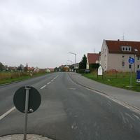 """Anfahrtsansicht von der """"Geschwindigkeitsdrosselungsinsel"""" am Ortseingang von Veitsbronn (Siegelsdorf) kommend, also in Fahrtrichtung Cadolzburg. Vorne rechts spitzt schon der silberne Peugeot aus der Einfahrt."""