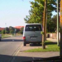 Unauffälliger grauer VW-Bus, gegenüber ein knallgelbes Haus zum Ablenken.