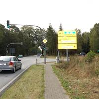 Übersichtsaufnahme. Eine Ampelkreuzung mit separater Linksabbiegespur für beide Richtungen, rechts im Hintergrund ein blauer VW Transporter und sehr unauffällig rechts im Bild am Laternenmast sind zwei Kameras angebracht.