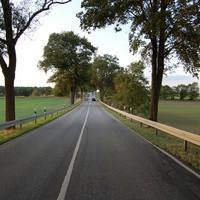 Anfahrt. Man kommt von einer viel frequentierten, mit 70 km/h limitierten Kreuzung den Berg hinab und die 70 werden nicht aufgehoben. Rechts steht ein dunkler Kombi, auffällig.