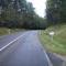 Anfahrtsansicht in Höhe des KM 3,0. Nach der Kurve fällt die Straße ein wenig ab. Es folgen ein 60er-Limit- und Parkplatzschild.