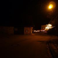 Anfahrtsansicht. Rechts liegt eine Gastwirtschaft, links mündet die Dillbergstraße.