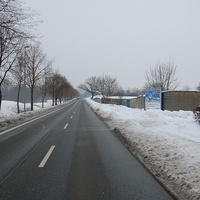 Anfahrtsansicht stadteinwärts. Lange schnurgerade Strecke mit breitem Bürgersteig und Radweg.