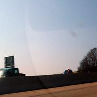 """Sehr, sehr schlechtes Bild von der Gegenfahrbahn. Dennoch mal eingestellt bis bessere Bilder vorhanden: Zu sehen ist das Messfahrzeug (BMW E39 Kombi) welches """"getarnt"""" hinter den Bäumen stand und so nicht zu sehen war. Kurz vor der Notrufsäule lassen sich das PSS und der abgesetzte Zusatzblitz erahnen - und die hatten viel zu tun!"""