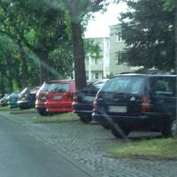 Silberner VW Bus in einer Parkeinbuchtung.