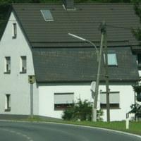 """Von Eslohe aus kommen wir zum Ortsteil """"Berge"""" mit GRÜNEM Ortsschild.In einer Linkskurve steht ein weisses Haus mit dunklem Dach.Der Blitzer steht direkt auf Höhe des Hauses."""