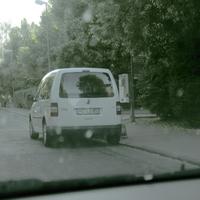 VW-Caddy weiß, Blitzgerät hinter der Heckscheibe, externes Meßgerät vor dem Gebüsch am rechten Fahrbahnrand