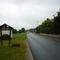 Dem Holzschild ist zu entnehmen, dass die Ortschaft beendet ist - man hat den Friedhof mit Fußgängerüberweg und eine Bushaltstelle passiert, wo eine gewisse Unfallgefahr zu sehen ist.