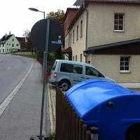 in der Einfahrt eines Grundstückes steht dieser blaue VW Caddy, die Blitzanlage ist entweder im Fahrzeug oder sie steht neben dem Zaun auf der Grundstücksseite