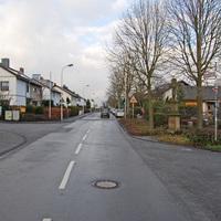 Die Aufnahme zeigt den Straßenverlauf der Meßdorfer Straße, der einstigen K 12, nach ihrer Abstufung und Eingliederung in eine 30er-Zone. Rechtsseitig ist das Gelände des örtlichen Kindergartens zu erkennen, der hier die Messbegründung darstellt.