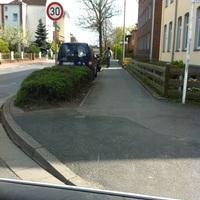 kaum zu erkennen - im Heck des blauen Autos steht die Leivtec. Der Messbeamte steht in der Sonne und telefoniert.