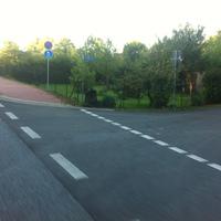 """am Strassenschild umhüllt mit einem Tarnnetz steht der """"Fotoapparat"""" und blitzt Fahrzeuge in Richtung ESSO / Steegener Chaussee. Messfzg. VW-Golf 4 silber steht in unmittelbarer Nähe."""