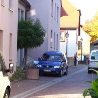Nahaufnahme des blauen VW Caddy in Richtung Friedhofstraße, der rote Blitz ist deutlich zu sehen! Die Radarantenne ist das schwarze rechteckige Kästchen mittig über dem Kennzeichen.