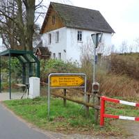 In Fahrtrichtung Lütjensee kurz vor der Bus-Haltestelle zwischen Wertstoff-Container versteckt steht der ES 3.0 Sensor. Der grüne Hochdach-Messbus steht rechts im Fußweg. Kamera und Wabenfilter-Blitz steht hinter der Fußweg-Absperrung...