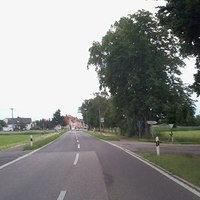 WLAN Kamera links mit Tarnnetz, Kamera rechts hinter Rad/Fußweg-Schild.