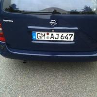 In Parklücke auf Gegenfahrbahn der Sürther Strasse 274 in Köln. Geblitzt wird in aus dunkelblauem Opel Astra Kombi, Fahrtrichtung stadteinwärts. Tempo 30 Schild ist zugewachsen. Das Blitzerfahrzeug hat vorne und hinten verschiedene Kennzeichen.