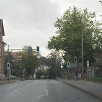 An der Ampel ist der Fußgängerüberweg der Grundschule. Die Strecke ist leicht abschüssig und wirkt breiter da es in diesem Straßenabschnitt keine parkenden Autos gibt.