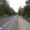 Auf dem Bürgersteig neben dem Plakat steht der Blitzer auf dem Stativ. Rechts auf dem Weg, schön im Park versteckt, steht der Messwagen, silberner Passat Kombi, Kennzeichen HS-NI 144.