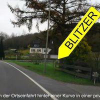 Der Blitzer steht direkt hinter einer Kurve nach der Ortseinfahrt nach Langenholdinghausen in einer privaten Hofeinfahrt. Nicht zu erkennen, denn wenn die Hecke den Blick freigibt ist es auch schon zu spät.