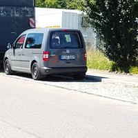 Grauer Caddy am Straßenrand hinter den Containern versteckt. Kennzeichen: M-AE-2009