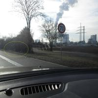 Mobiler Blitzer: Fahrzeug (VW Caddy, schwarz) vom Gebüsch verdeckt, Anlage nur schwer zu erkennen.