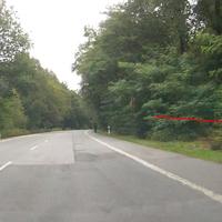 Messung mit Lichtschranke, Fahrzeug steht dahinter im Wald und hat keine freie Sicht auf Fahrbahn. Das links stehende nicht auf diesem Photo sichtbare Fahrzeug ist leer und steht dort öfter. Die Polizei steh als rechts hinter dem Blitzer im Wald.