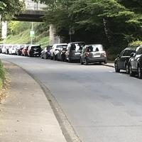 Blitzer Caddy der Stadt versteckt sich zwischen den parkenden Autos und im Schatten der Brücke